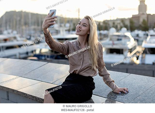 Smiling young woman taking a selfie at the waterfront