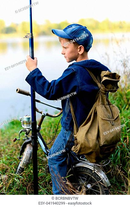 A child on a bicycle with a backpack on the shore of the river with fishing accessories.It stands on the river bank with a backpack and a bicycle and a fishing...