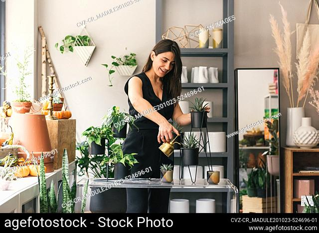 Woman entrepreneur in her flower shop as she finishes plant display