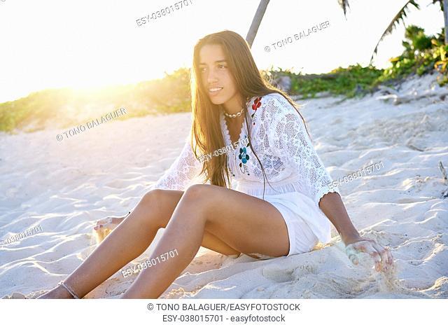 Latin beautiful girl sunset in Caribbean beach sand sitting relaxed