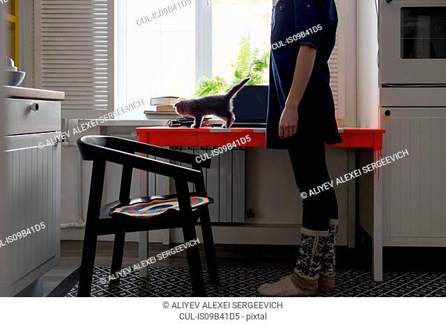 Woman watching kitten on kitchen table