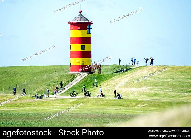 28 May 2020, Lower Saxony, Pilsum: Tourists walk on the dike in front of the Pilsum lighthouse in the municipality of Krummhörn
