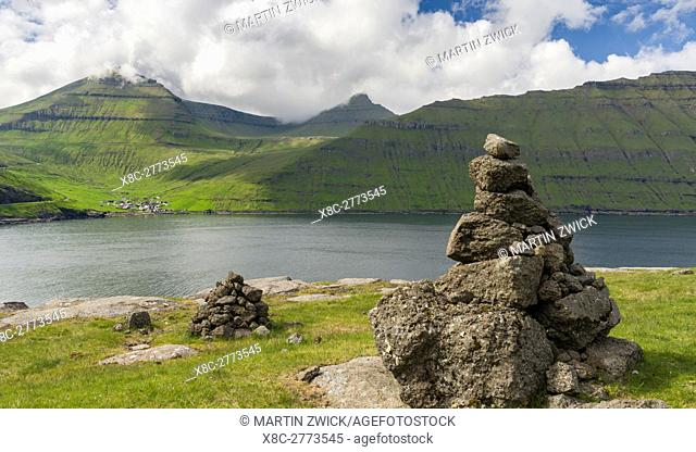 Old traditional cairns, in the background mount Slaettaratindur, the highest peak in the Faroe and village Funningur located at the Funningsfjordur