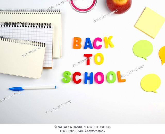 inscription back to school from multi-colored plastic letters and a stack of notebooks with blank white sheets on a white background, top view