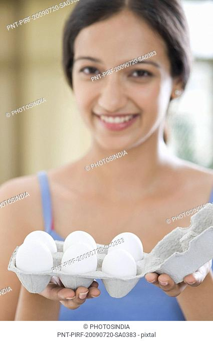 Woman holding a carton of eggs and smiling