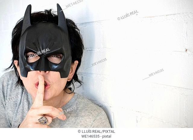Young woman with a Batman mask and expression of silence