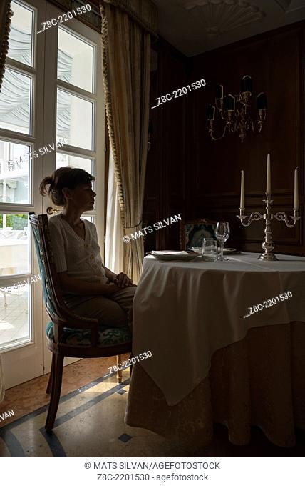 Woman sitting at a table with candlestick and window light in Rimini, Italy