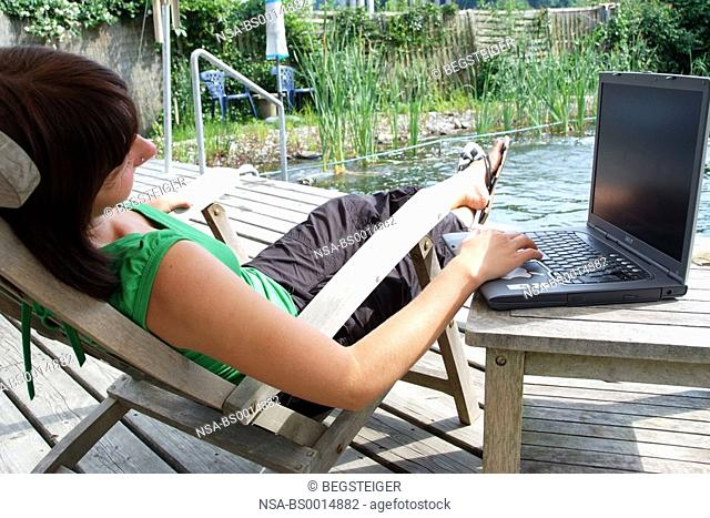 woman with laptop at pond