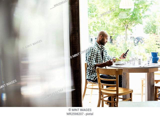 Man wearing a checked shirt sitting in a cafe, using his mobile phone
