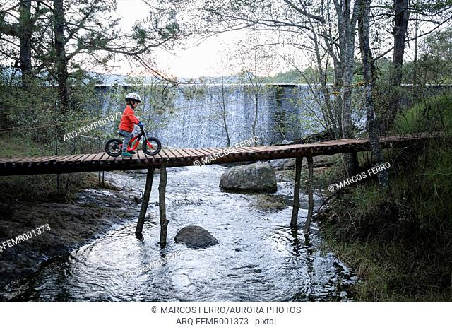 Side view of three year old boy riding bicycle over footbridge, Rancho Santa Elena, Hidalgo, Mexico