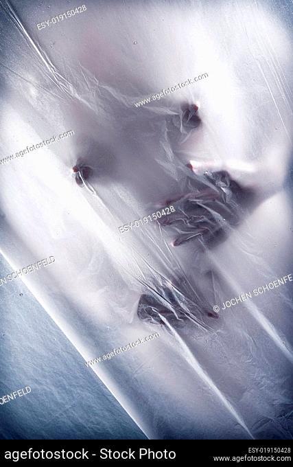 Junge Frau, sich berührend hinter transparentem Vorhang
