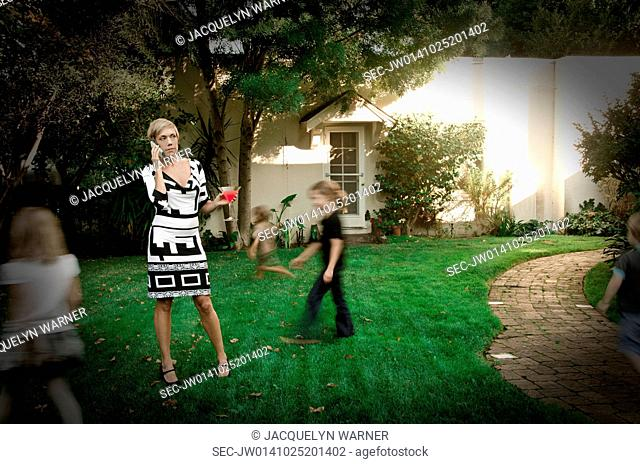 Mother standing on garden lawn talking on phone and children wandering around