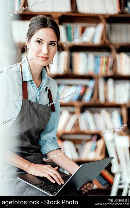 Confident female entrepreneur with laptop in coffee shop
