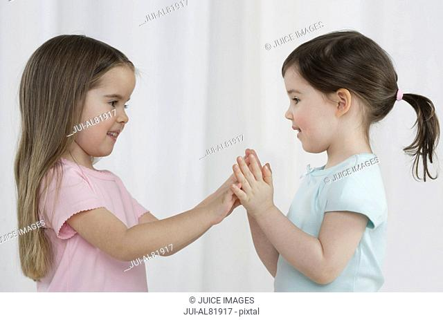 Two young sisters playing indoors