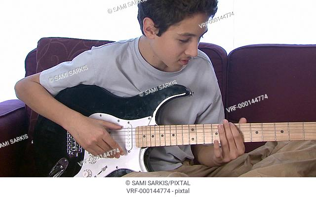 Boy 13-14 playing electric guitar