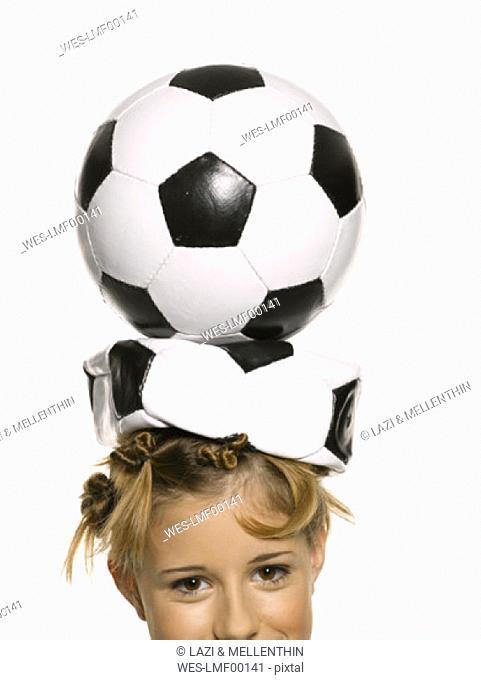 Girl balancing a football on her head