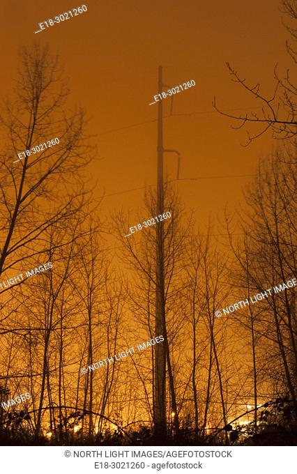 Canada, BC, Delta. Night sky lit up with light pollution from industrial area beside the Fraser River. Suburban area close to Vancouver