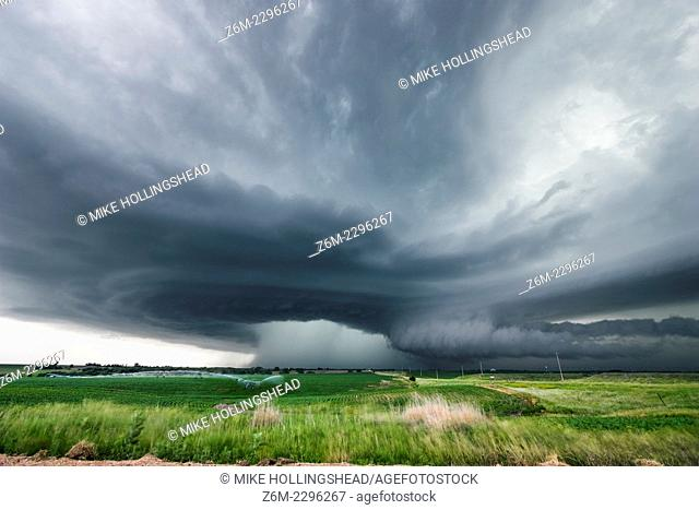 High precipitation supercell storm tracks south of Hastings Nebraska June 15, 2009 as irrigation pivot waters the field ahead of the storm