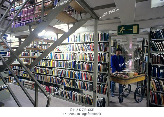 Europe, Germany, Bavaria, Munich, Bavarian State Library, library assistant with a book mobile in a book stack