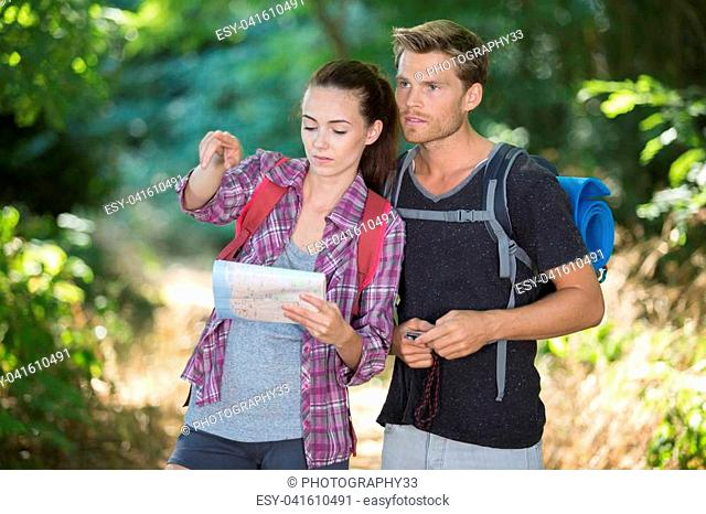 young couple hiking trough forest and watching birdsornithology