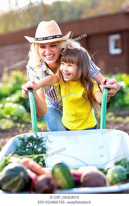 Mother and Daughter pushing Wheelbarrow with Harvest