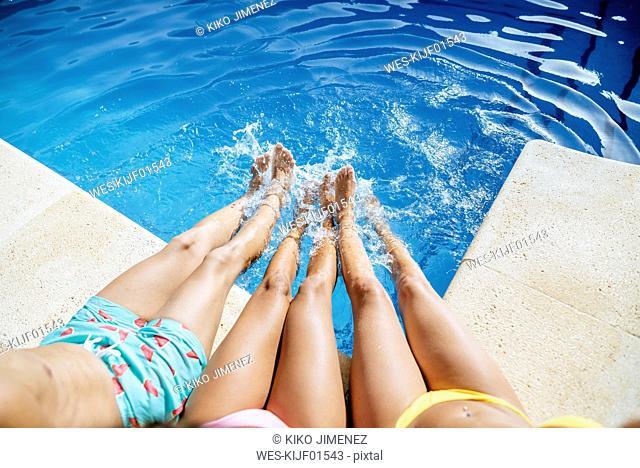 Legs of friends splashing in pool