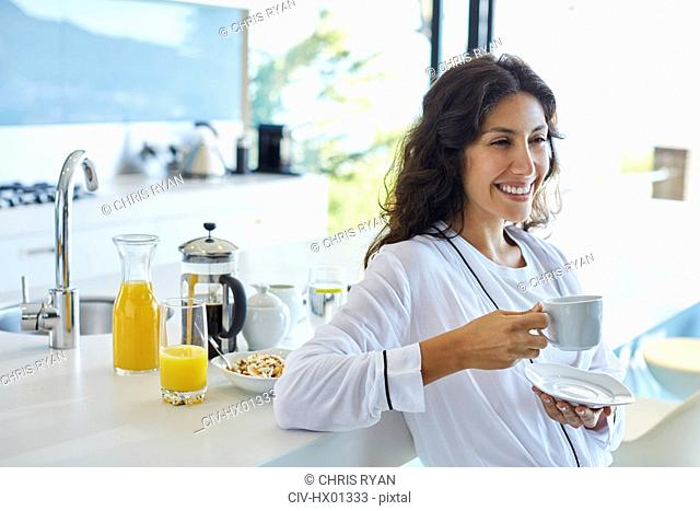 Smiling woman in bathrobe drinking coffee in morning kitchen