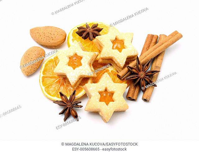Christmas cookies, spices, alomonds and dry orange slices on white background