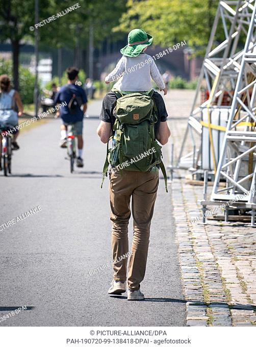 16 July 2019, Hessen, Frankfurt/Main: A man carries a child on his shoulders and a backpack on his back. Photo: Frank Rumpenhorst/dpa