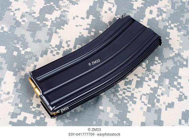 M16 rifle magazine with cartridges on camouflage uniform background