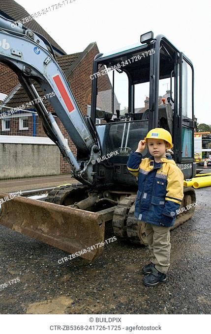Boy standing near mini digger