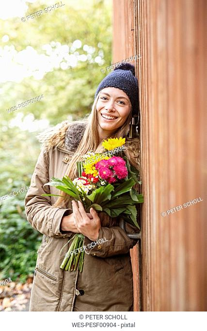 Portrait of smiling young woman holding bunch of flowers outdoors
