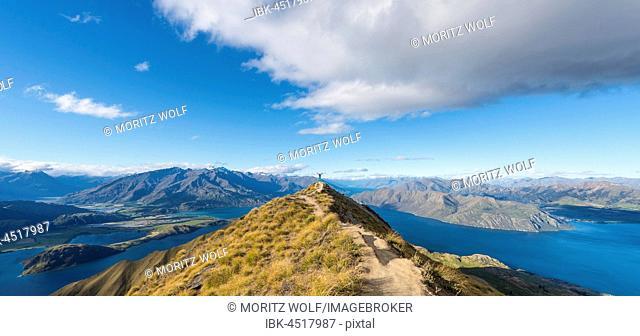 View of mountains and lake, woman standing on top ridge, Roys Peak, Lake Wanaka, Southern Alps, Otago Region, Southland, New Zealand