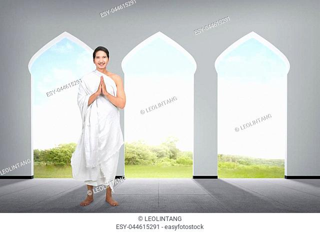 Religious asian muslim man with hand gesture on the mosque