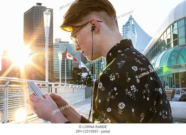 Teenage boy using his smart phone and wearing earbuds in downtown Vancouver; Vancouver, British Columbia, Canada