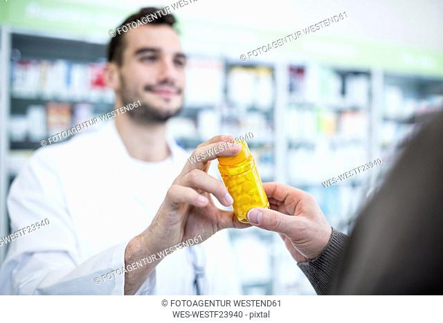 Close-up of harmacist giving pill box to customer in pharmacy