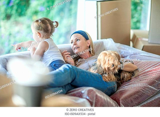 Moving house: mother daughter and pet dog relaxing on bubble wrapped sofa