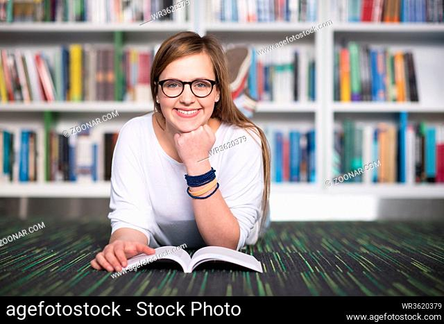 female student study in school library, using tablet and searching for information?s on internet. Listening music and lessons on white headphones