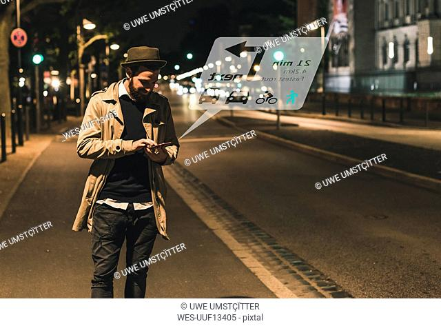 Young man on street at night with data emerging from smartphone