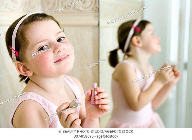 Little girl applying make up