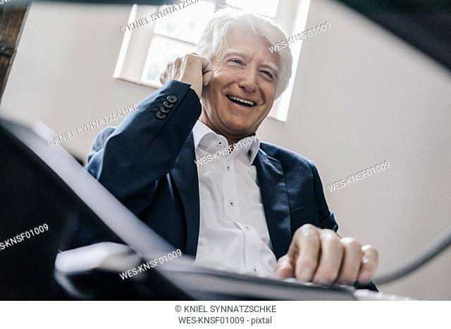 Portrait of laughing senior businessman on the phone in his office