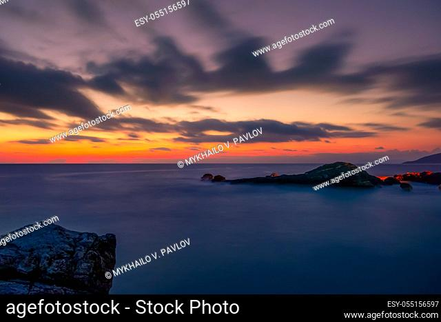 Rocky shore of the sea. Colorful sunset in the sky with clouds