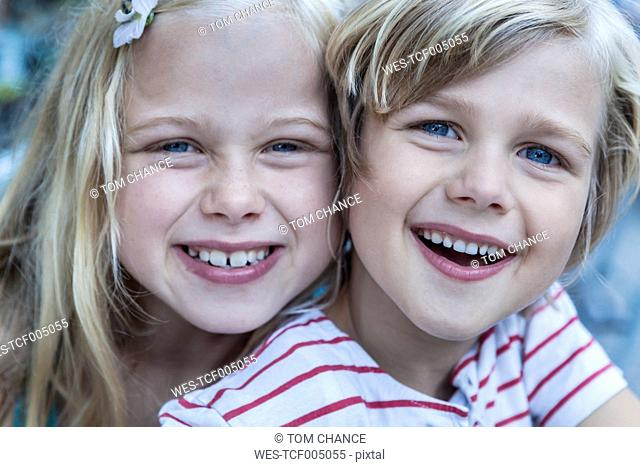 Portrait of smiling little boy and his sister head to head