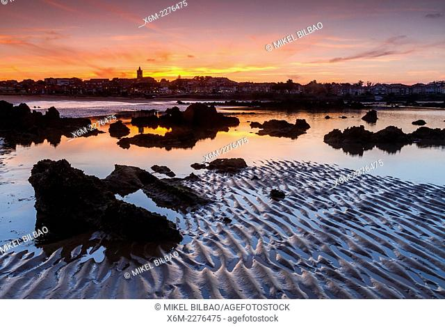 Rocky beach and village at dusk. Trengandin beach. Noja, Cantabria. Spain, Europe