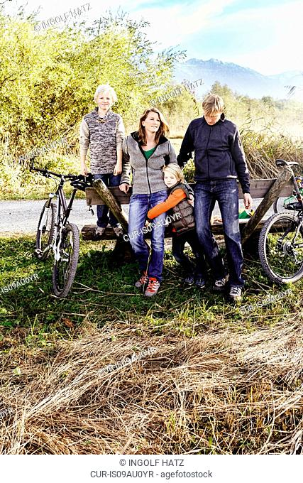 Family with bicycles leaning against bench by roadside