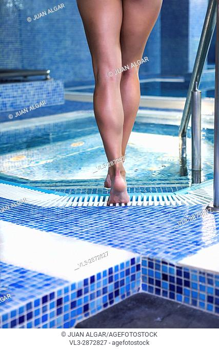 Back view of female legs walking into pool. Vertical indoors shot