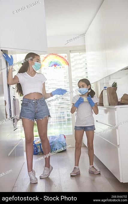 2 girls with masks and gloves arranging groceries