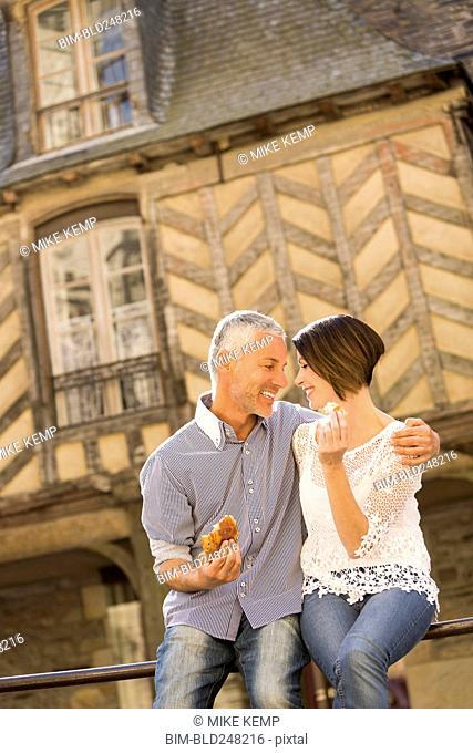 Caucasian couple eating bread on railing