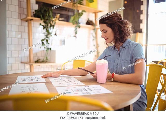 Young woman sitting with papers and drink at coffee shop