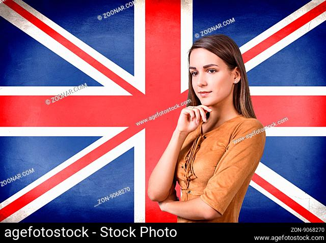 Young woman standing on the UK flag background